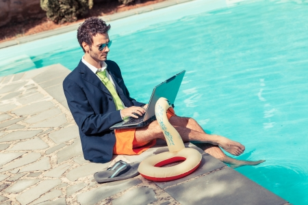 swim suit: Funny Young Businessman with SwimmingTrunks next to the Pool