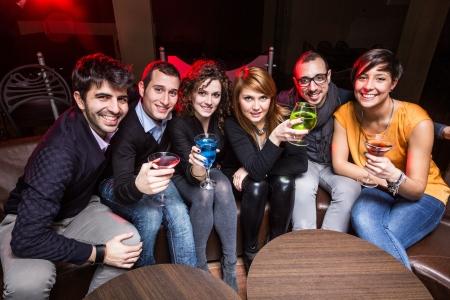 jovenes tomando alcohol: Grupo de amigos en un club de noche Foto de archivo