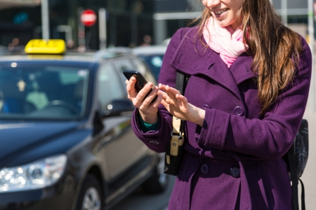 business traveler: Young Woman Talking on Mobile waiting for Taxi Stock Photo