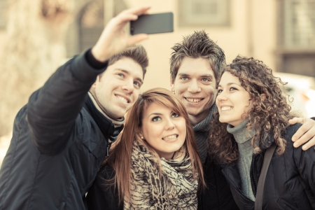Group of Friends taking Self Portraits with Mobile Phone photo