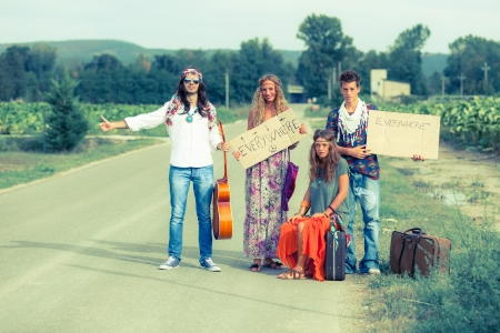 70s adult: Hippie Group Hitchhiking on a Countryside Road
