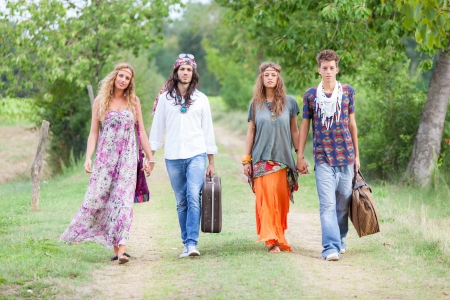 70s adult: Hippie Group Walking on a Countryside Road