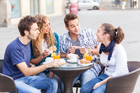 white bars: Group of Friends Having a Traditional Italian Breakfast Stock Photo