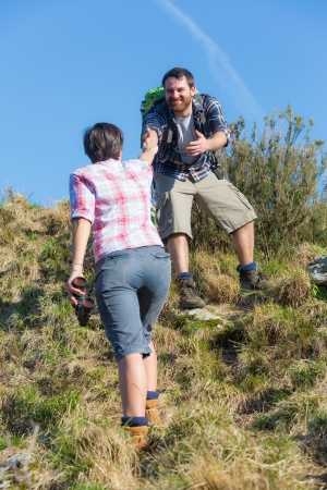 Man Helping His Girlfriend Hiking photo