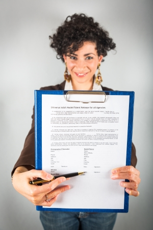 holding blank sign: Young Businesswoman Showing a Contract to Sign