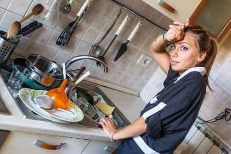lavar trastes: Lavar los platos Criada en la cocina