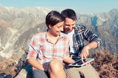 views of the mountains: Couple with Digital Tablet at Top of Mountain