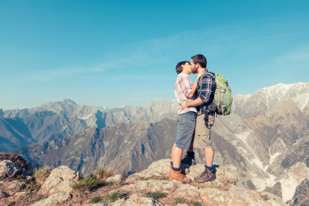 Couple Kissing at Top of Mountain photo