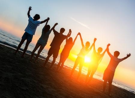 Grupo de personas con los brazos levantados mirando la puesta del sol Foto de archivo