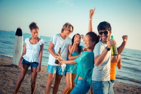 hombre tomando cerveza: Grupo de amigos que una de las Partes en la playa