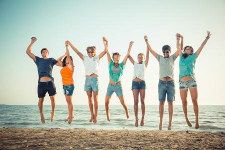 grupo de personas: Multiétnico grupo de personas saltando en la playa