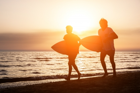 sand surfing: Two Boys with Surf Boards at Sunset