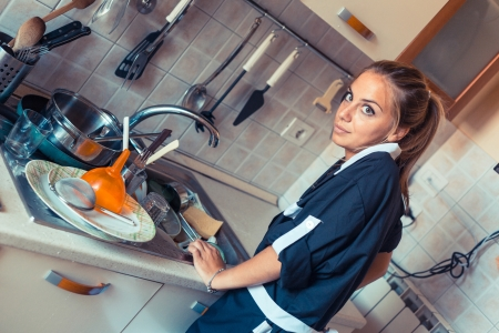 Housemaid Washing Dishes in the Kitchen photo
