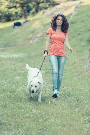 Young Woman Walking with Her Dog photo