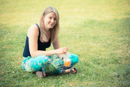 lithuanian: Blonde Woman Drinking Fruit Juice at Park