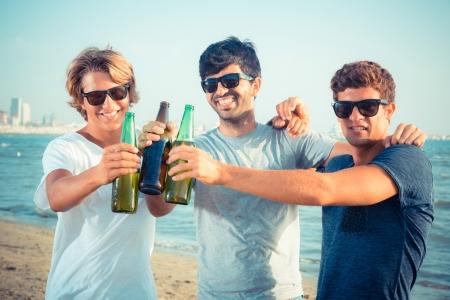 hombre tomando cerveza: Grupo de muchachos que animan en la playa