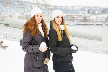 Two Women playing with Snow on Winter photo