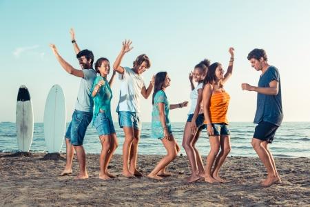 manos levantadas al cielo: Grupo de amigos con una fiesta en la playa