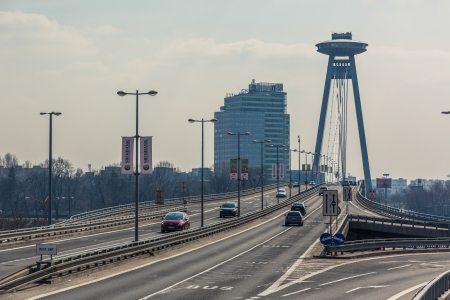 slovak republic: BRATISLAVA, SLOVAKIA - MARCH 23: New futuristic bridge with skyscrapers on background on March 23, 2013 in Bratislava, Slovakia.