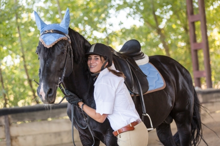 girl on horse: Young Woman with a Black Horse Stock Photo