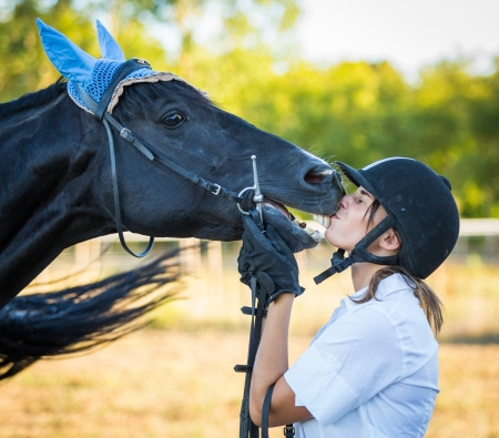 Young Woman Kissing a Black Stallion Horse photo