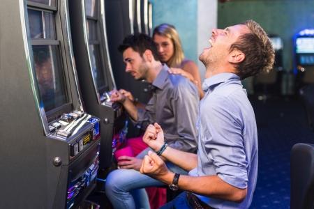 maquinas tragamonedas: Grupo de amigos de juego con m�quinas tragamonedas Foto de archivo