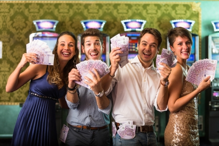 excited: Friends Winning a lot of Money at Casino Stock Photo