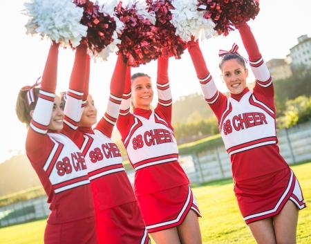 pom pom: Group of Cheerleaders with Raised Pompom Stock Photo