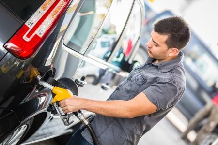 fuelling station: Hombre joven que llena su coche en la gasolinera Foto de archivo