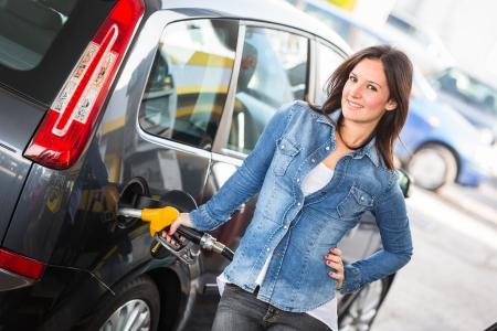 Jonge vrouw vullen haar auto bij het benzinestation