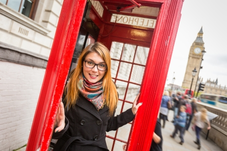 telephone booth: Young Woman next to London Traditional Telephone Booth