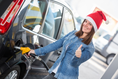 fueling: Young Woman with Santa Hat at Gas Station Stock Photo