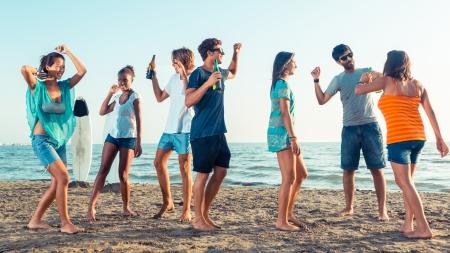 gens qui dansent: Groupe d'amis ayant une partie sur la plage Banque d'images