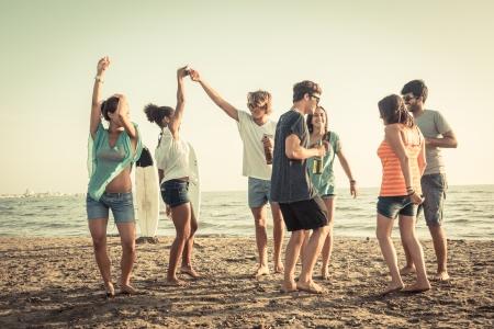amie: Groupe d'amis ayant une partie sur la plage Banque d'images