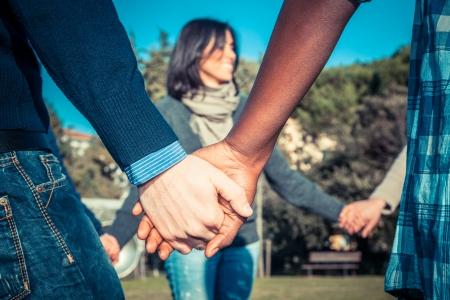 Multikulturelle Jugend Händchen haltend in einem Kreis Standard-Bild