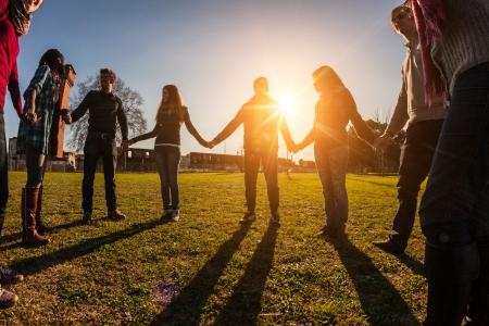 Multiraciale jongeren hand in hand in een cirkel