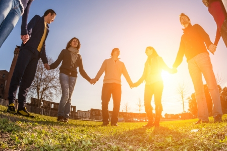 community: Multiracial Young People Holding Hands in a Circle Stock Photo