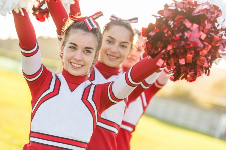 pom: Group of Cheerleaders with Raised Pompom Stock Photo