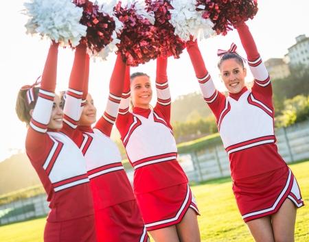 pom: Group of Cheerleaders with Raised Pompom Stock Photo