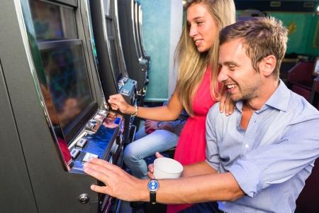 スロット マシンで遊んでの友人のグループ
