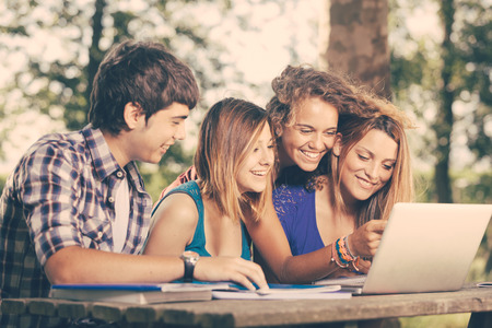 college campus: Group of Teenage Students at Park with Computer and Books Stock Photo