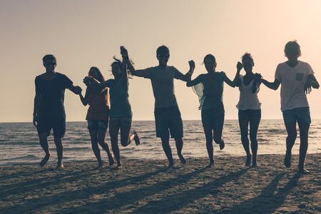 Group of People Running on the Beach at Sunset Stock Photo - 25641772