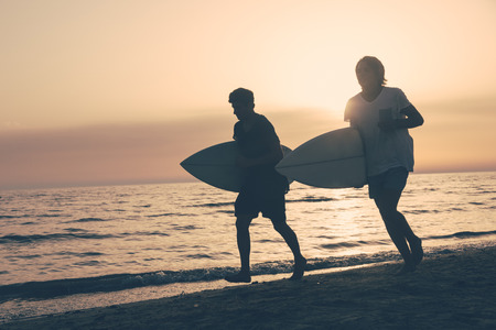 Two Boys with Surf Boards at Sunset Stock Photo - 25641811