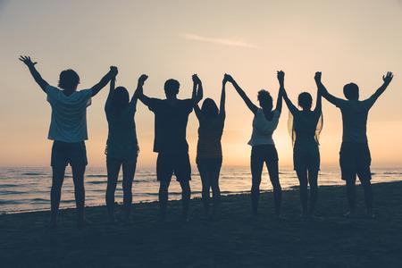manos levantadas: Grupo de personas con los brazos levantados mirando la puesta del sol Foto de archivo