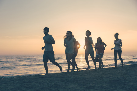 Group of People Running on the Beach at Sunset photo