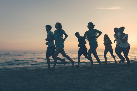 Group of People Running on the Beach at Sunset Stock Photo - 25641899
