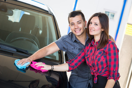 Young Couple Washing Car Together photo