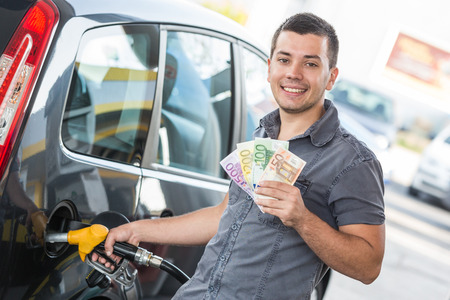 Man with Banknotes at Gas Station Stock Photo