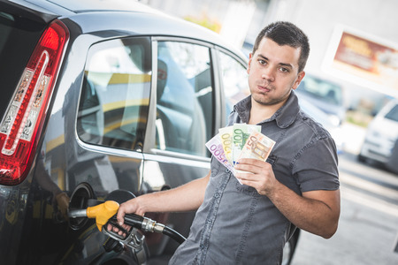 gasoil: Man with Banknotes at Gas Station Stock Photo