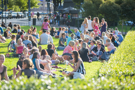 finland: HELSINKI, FINLAND - JUNE 28, 2013: Young people resting at park on a sunny day
